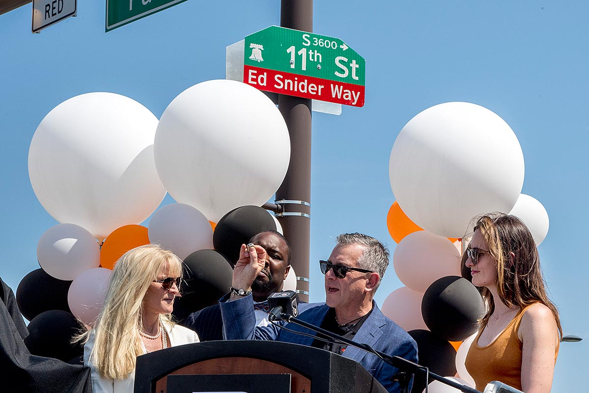 Craig Snider, son of the late Flyers founder and Comcast Spectacor chairman Ed Snider, holds up one of his father's Stanley Cup Championship rings at a ceremony May 18, 2017, where the city renamed a portion of 11th St. to Ed Snider Way. On stage with Snider are his sisters Lindy Snider (left) and Sarena Snider (right) and councilman Kenyatta Johnson (background) who was instrumental in getting the name change accomplished.