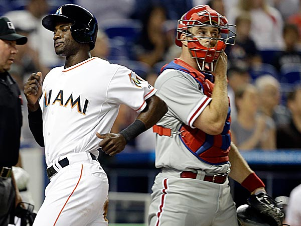 The Marlins´ Adeiny Hechavarria passes Phillies catcher Erik Kratz to score in the first inning. (Lynne Sladky/AP)