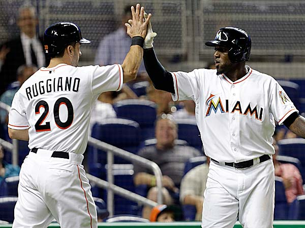 The Marlins´ Justin Ruggiano and Marcell Ozuna high-five after scoring on a single by Nick Green in the eighth inning. (Lynne Sladky/AP)