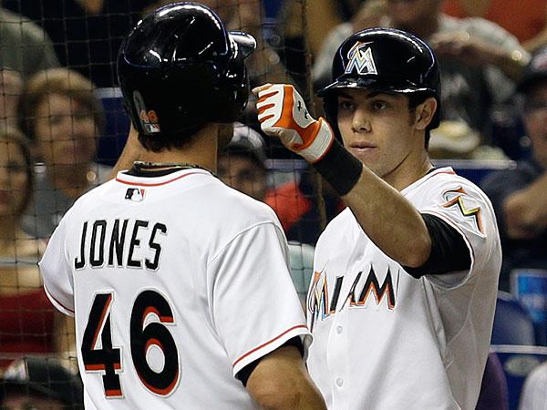 The Marlins´ Garrett Jones is congratulated by Christian Yelich after Jones scored on a base hit. (Alan Diaz/AP)