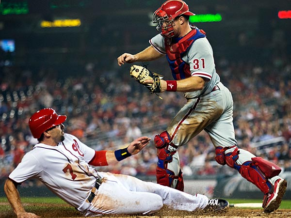 Philadelphia Phillies catcher Erik Kratz (31) evades the slide by Washington Nationals´ Mark DeRosa (7) as DeRosa is forced out at home during the eighth inning of a baseball game in Washington, Tuesday, Oct. 2, 2012. The Nationals won 4-2. (AP Photo/Manuel Balce Ceneta)