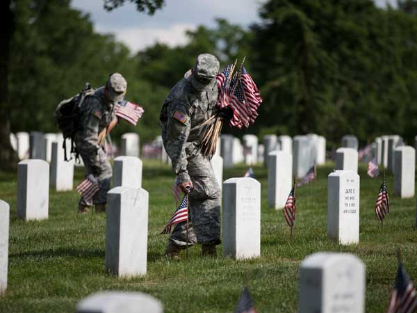 """Soldiers with the 3rd U.S. Infantry Regiment, also known as The Old Guard, places flags at grave sites at Arlington National Cemetery as part of the annual """"Flags-In"""" ceremony in preparation for Memorial Day on Thursday, May 23, 2013, in Arlington, Va. (AP Photo/Evan Vucci)"""