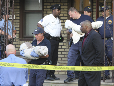 Police remove the bodies of twin toddlers on the 6300 block of Ditman Street in the Northeast on Thursday. (Steven M. Falk / Staff Photographer)