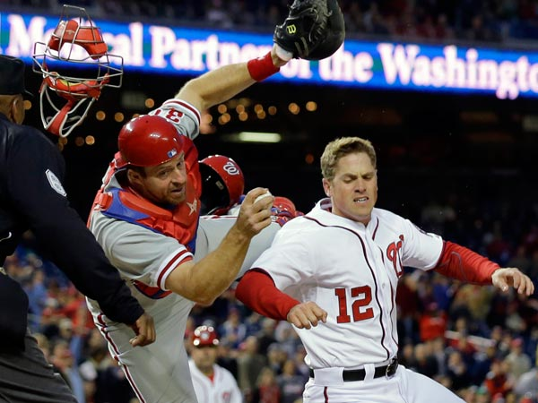 Erik Kratz (31) hangs on to the ball to make the tag on Washington Nationals´ Tyler Moore (12) for the out at home during the fourth inning of a baseball game at Nationals Park, Friday, May 24, 2013, in Washington. (Alex Brandon/AP)