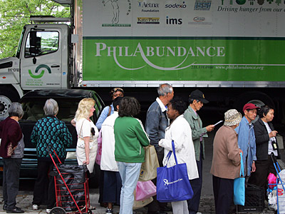 People line up under I-95 for free food from Philabundance on Monday afternoon. (David Swanson / Staff Photographer)