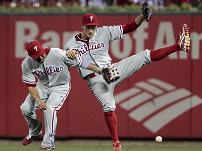 Shane Victorino and Hunter Pence collide as they chase a fly ball in the fourth inning on Friday. (Jeff Roberson/AP)