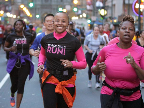 "Beverly Brown (center) smiles as she runs with the running group ""Black Girls Run"" during a run from City Hall down Market St. to Independence Mall to show support for folks in Boston on April 18, 2013. (Elizabeth Robertson/Staff Photographer)"