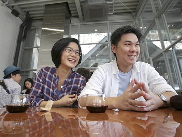 In this April 27, 2015 photo,  Michael Lin, 35, right, and Emily Chiu, 33, left, both travelers from Taipei, speak during an interview at a coffee shop of Blue Bottle Coffee Inc., in Tokyo. Japan, famous for green tea, is welcoming artisanal American coffee roaster Blue Bottle with long lines that have at times meant a four-hour wait for a cup. (AP Photo / Shuji Kajiyama)