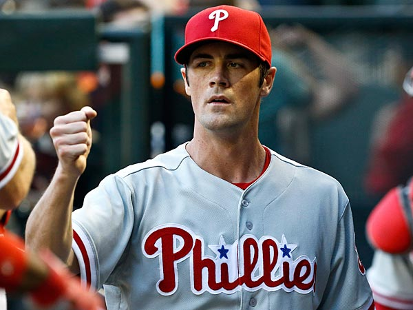 Philadelphia Phillies´ Cole Hamels, left, gets a fist pump ready as he walks in the dugout after warming up in the bullpen with catcher Carlos Ruiz, right, prior to a baseball game against the Arizona Diamondbacks on Thursday, May 9, 2013, in Phoenix. (AP Photo/Ross D. Franklin)
