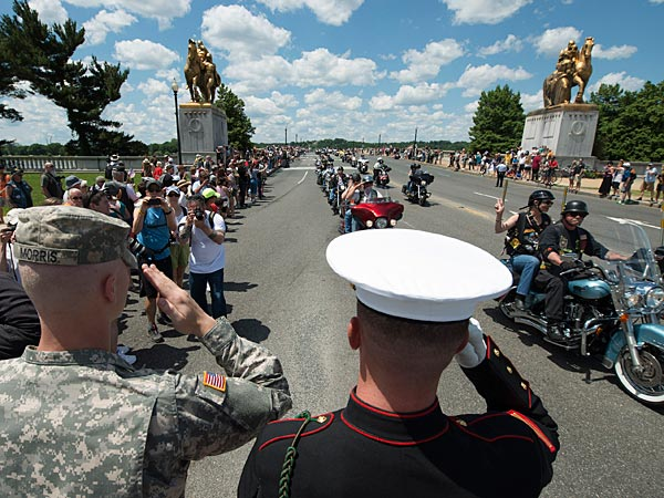 Army Pfc. Colin Morris, left, and Marine Cpl. Zach Powers, center, salute participates of Rolling Thunder ´Ride for Freedom´ event in Washington, Sunday, May 25, 2014. (AP Photo/Molly Riley)