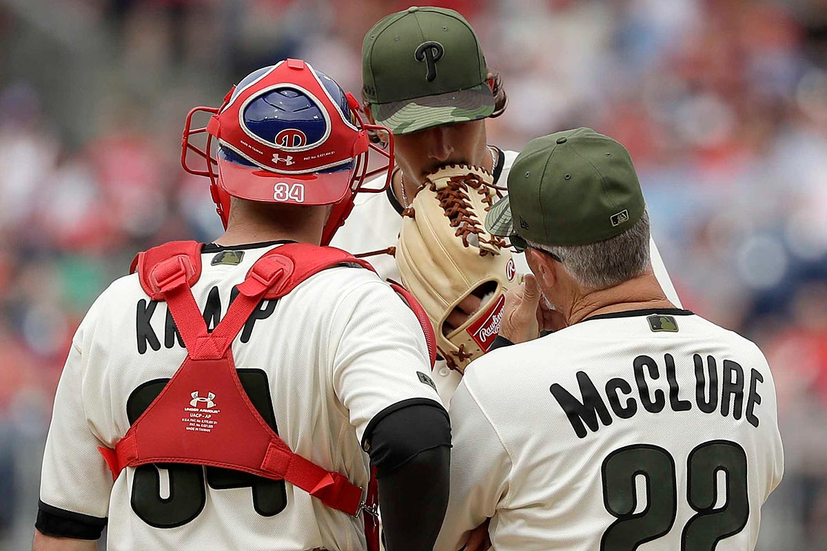 Phillies pitcher Zach Eflin meets with pitching coach Bob McClure and catcher Andrew Knapp.