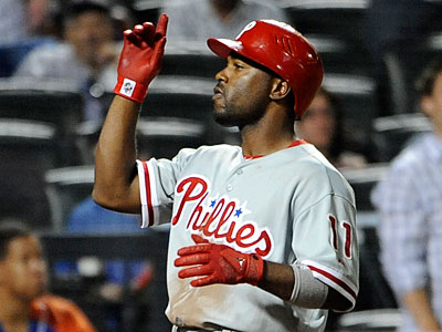 Jimmy Rollins points skyward as he rounds the bases after hitting a three-run homer. (Kathy Kmonicek/AP Photo)