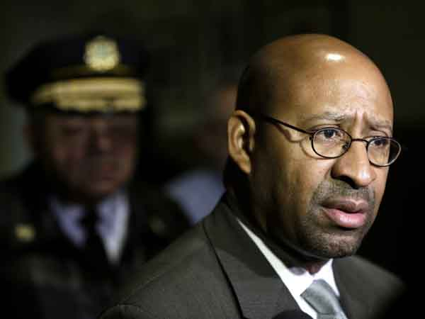 Philadelphia Mayor Michael Nutter accompanied by Police Commissioner Charles Ramsey, left, speaks during a news conference at City Hall in Philadelphia.