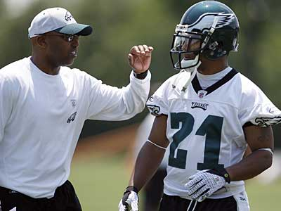 New Eagles assistant coach Brian Stewart, left, pats Joselio Hanson, right, on the back during today´s workout at the NovaCare Complex. Veteran cornerback Sheldon Brown was a no-show. (David Maialetti / Staff Photographer)