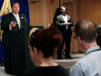 Gov. Chris Christie answers a question June 2 in Denville, NJ. That´s my head to the right, by the way, and the Star-Ledger´s Ginger Gibson to the left, but you probably don´t care about that. (AP Photo / Mel Evans)
