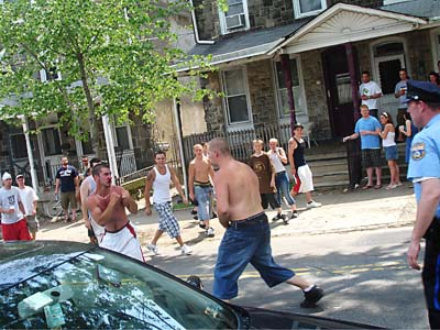 Two men duke it out in the middle of Manayunk Avenue at the end of the bike race in 2008. A police officer prepares to break up the fight. (Vance Lehmkuhl / Philly.com)