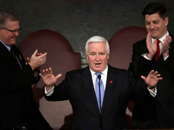 Gov. Corbett, joined by Speaker of the House Sam Smith (left) and Lt. Gov. Jim Cawley, draws applause at a joint session of the Pennsylvania House and Senate. Corbett offered a plan without spending cuts this time. MATT ROURKE / Associated Press