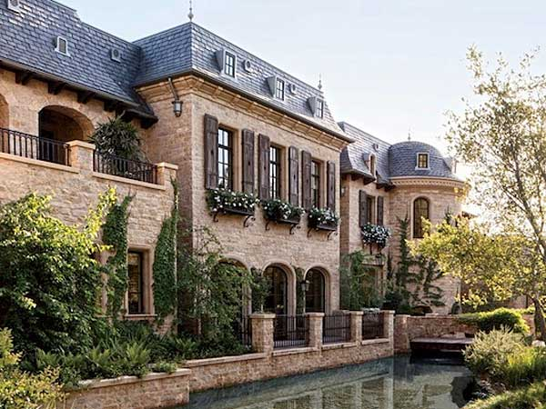 A blend of three types of Texas limestone gives the exterior walls a castle-like feel. To top it off, a bridge serves as a path to the front entrance. (via PopSugar)
