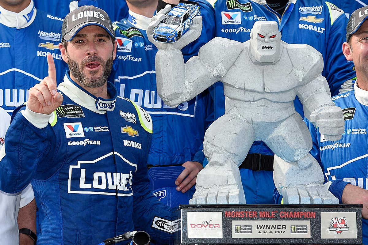 Jimmie Johnson, left, poses with the trophy in Victory Lane after he won a NASCAR Cup series auto race, Sunday, June 4, 2017, at Dover International Speedway in Dover, Del.