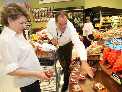Acme Markets opened a brand new supermarket in Bryn Mawr at the site of its former store.  Manager Nick Caridesright helps a customer in the produce section. (Charles Fox / Staff Photographer)