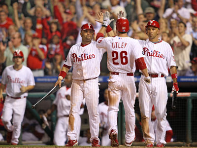 Chase Utley is greeted at the plate by Placido Polanco and Raul Ibanez. The Phillies beat the Marlins, 10-8. (David M Warren / Staff Photographer)