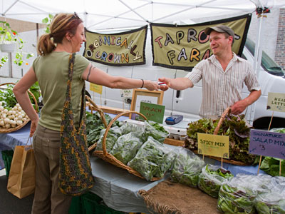 An Desaeger of Elkton, Md., completes a purchase from George Brittenburg at his Taproot farm stand at South and Passyunk Farmer's Market. (David M Warren / Staff Photographer)