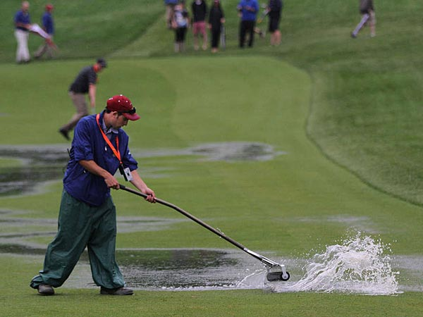 A grounds worker uses a squeegee to dry the 16th fairway at Merion. (Michael Bryant/Staff Photographer)