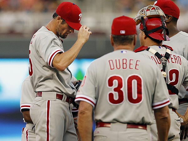Phillies pitching coach Rich Dubee (30) approaches the mound to talk to starting pitcher Cole Hamels, left, during the fourth inning of a baseball game against the Minnesota Twins, Tuesday, June 11, 2013, in Minneapolis. (Genevieve Ross/AP)