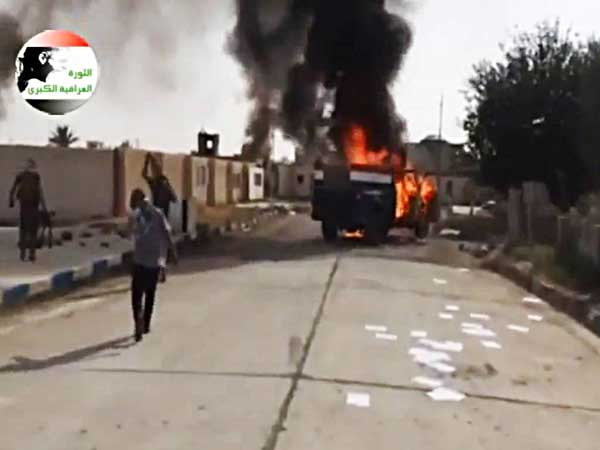 This image made from video posted by Iraqi0Revolution, a group supporting the al-Qaida breakaway Islamic State of Iraq and the Levant (ISIL) on Wednesday, June 11, 2014, which has been verified and is consistent with other AP reporting, shows militants on Al-Sharqat base north of Tikrit, Iraq. The al-Qaida-inspired group that led the charge in capturing two key Sunni-dominated cities in Iraq this week has vowed to march on to Baghdad, raising fears about the Shiite-led government's ability to slow the assault following lightening gains. Fighters from ISIL on Wednesday took Saddam Hussein´s hometown of Tikrit, as soldiers and security forces abandoned their posts and yielded ground once controlled by U.S. forces. (AP Photo/Iraqi0Revolution via AP video)