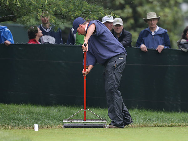 A member of Merion´s ground crew uses a squeegee to dry out the back of the 16th tee after Thursday morning´s storms. (Michael Bryant/Staff Photographer)