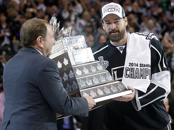 Kings right wing Justin Williams, right, is handed the Conn Smythe Trophy by NHL commissioner Gary Bettman, left, after the Kings beat the Rangers in Game 5 of the NHL Stanley Cup Final series Friday, June 13, 2014, in Los Angeles. (Jae C. Hong/AP)