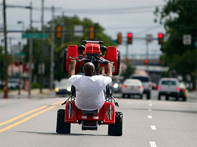 An ATV rider wheelies down Lehigh Avenue on a recent Sunday.  (David Maialetti / Staff Photographer)
