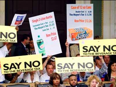 Opponents (left) of a proposal to tax soda and other sugary drinks display signs at a City Council hearing earlier today, (AP Photo/Matt Rourke)