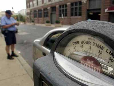 A Philadelphia Parking Authority enforcement officer writes a ticket for a car parked at an expired meter. (File photo)