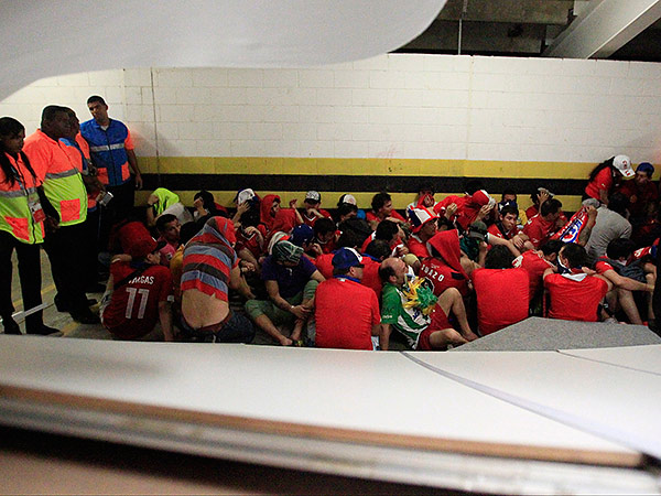 Chile fans without tickets charged through the press center prior to the group B World Cup soccer match between their team and Spain at the Estádio do Maracanã in Rio de Janeiro. (Frank Augstein/AP)