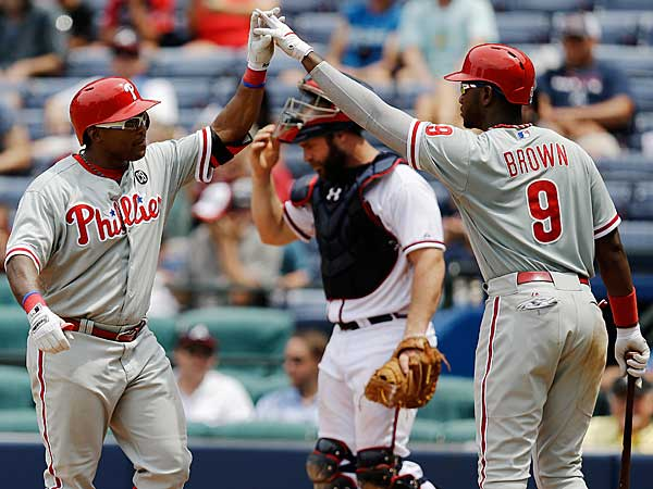 Marlon Byrd, left, is high-fived by teammate Domonic Brown after hitting a home run in the eighth inning of a baseball game against the Atlanta Braves, Wednesday, June 18, 2014, in Atlanta. (David Goldman/AP)