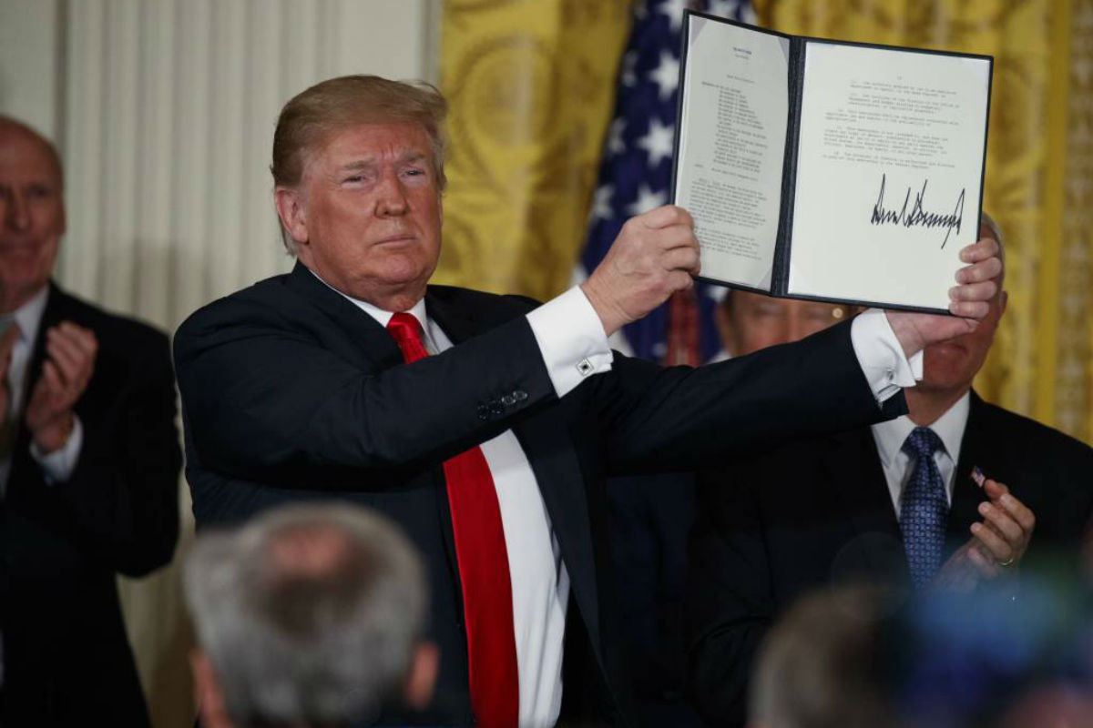 "President Donald Trump shows off a ""Space Policy Directive"" after signing it during a meeting of the National Space Council in the East Room of the White House, Monday, June 18, 2018, in Washington."