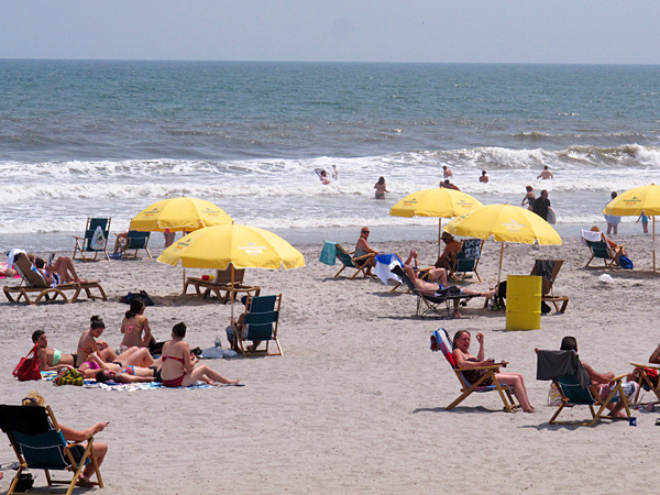 In this June 27, 2013 photo, beachgoers enjoy a sunny day on the beach in Atlantic City, N.J. The city is one of five Jersey shore beach towns that don´t require visitors to buy beach badges. (AP Photo/Wayne Parry)