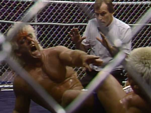 A bloody Ric Flair suffering from a figure-four leg lock. (Photo courtesy of the WWE Network)