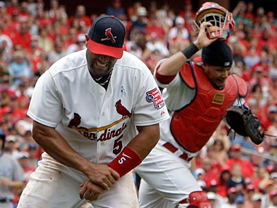 Cardinals first baseman Albert Pujols (left) grabs his left wrist after being injured on a play at first base. (Jeff Roberson/AP)