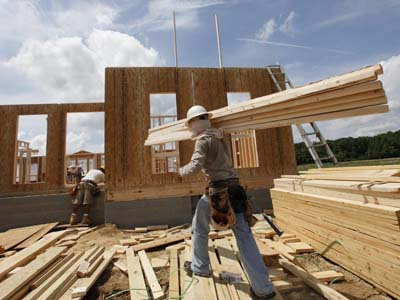 A construction worker carries a load of wood to a new home as they frame the house in Chester, Va. (AP File Photo / Steve Helber)