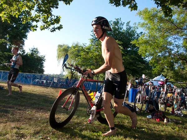 Brian MacIlvain, a 28-year-old elite competitor from Boston, transitions from swimming to biking during the 2012 Philadelphia Triathlon. New security checks will be in place at the transition area this year. (Abi Reimold / Staff Photographer)