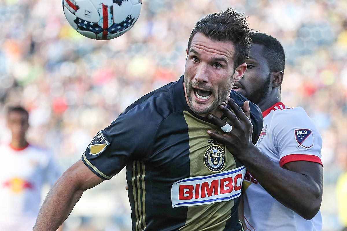 Union forward Chris Pontius keeps his eye on the ball with New York Red Bulls defender Kemar Lawrence.