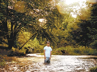"Josh Fox standing in a stream near Dimock, Pa., where residents´ animals began to lose their hair after drilling started, presumably from drinking contaminated water. It is part of ""Gasland."""