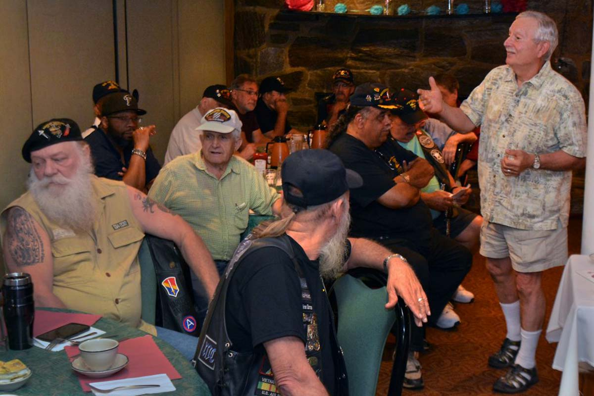 """Retired VA social worker Tony Capone (right) leads a veterans PTSD peer support group at the Garden State Diner in Wrightstown, NJ,  Monday mornings.  On the left, Leo """"Smooth"""" Ethier, one of the group founders, sits at a table next to another founder, Lynn """"Mo Aces"""" Moyer (back turned)."""