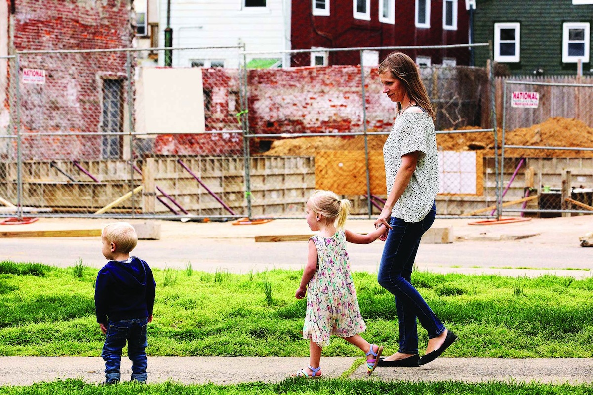 File: Jana Curtis and her children walk past a construction site next to their neighborhood park.