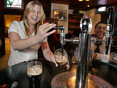 Frances Bevan pours her own beer, during happy hour, at Tir na Nog, the pub inside the Phoenix at 16th and Arch streets in Philadelphia. (Elizabeth Robertson / Staff Photographer)