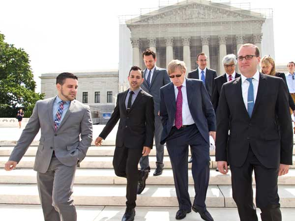 Chad Griffin, right, president of the Human Rights Campaign, leaves the Supreme Court, with Jeff Zarrillo, left, and Paul Katami, second from left, the plaintiffs in the California Proposition 8 case, and their attorney Ted Olson, center, on June 20. (AP photo)