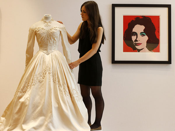 A Christie´s employee adjusts Elizabeth Taylor´s first wedding dress, designed by the legendary costume designer Helen Rose, at the auction house Christie´s in London, Wednesday, June 19, 2013. The wedding dress is part of the auction 120 years of Pop Culture, which is showcasing important memorabilia dating from every decade of the past century of popular culture from the ubiquitous industries of film and music. The estimated price is 30,000 ñ 50,000 pound (46,000-78,000 dollars). (AP Photo/Frank Augstein)