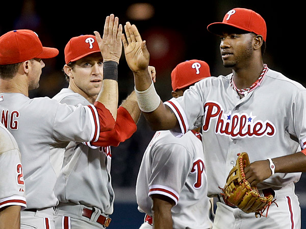 Philadelphia Phillies´ Domonic Brown, right, high fives with Michael Young, left, and Chase Utley after the Phillies´ 6-2 victory over the San Diego Padres. (AP Photo/Lenny Ignelzi)